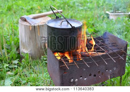 The kettle with a food on a brazier