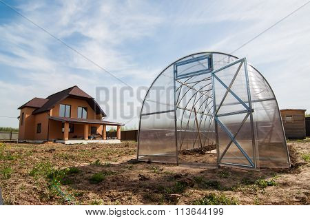 greenhouse on the property with a cottage house in spring