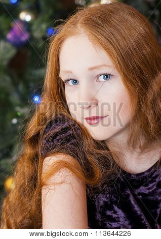 Portrait of a redheaded girl near a Christmas tree