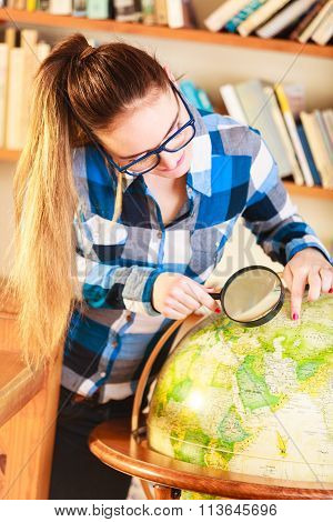 Girl In Library With Globe And Magnifying Glass