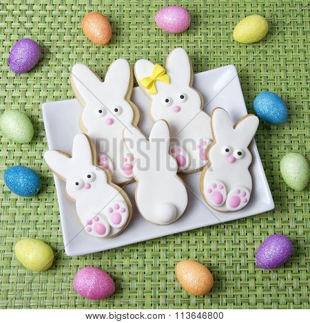 Easter bunny decorated sugar cookies on rectangle plate on green place mat