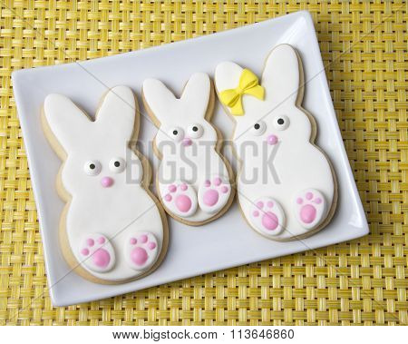 Sugar cookie Easter bunnies decorated on rectangle plate yellow place mat