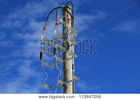 Power isolator switch manual on electrical pylon against the blue sky