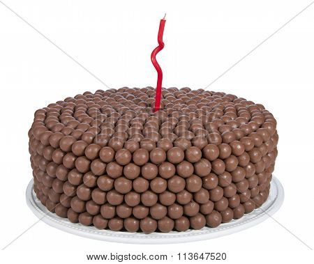 Chocolate cake decorated with rows of malt balls and one single red curvy candle