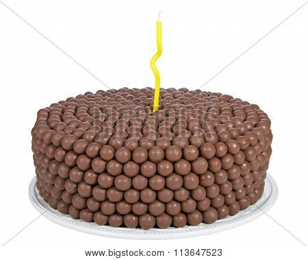 Chocolate cake decorated with rows of malt balls and one single yellow curvy candle