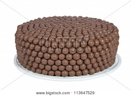 One whole chocolate cake decorated with rows of malt balls on a plate isolated on white background