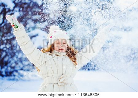 Little Girl Playing With Snow. Falling Snow Around The Child. Happy Childhood And Freedom Concept.
