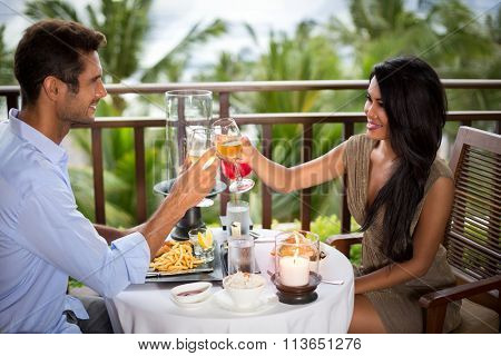Romantic couple on the balcony toasting during dinner