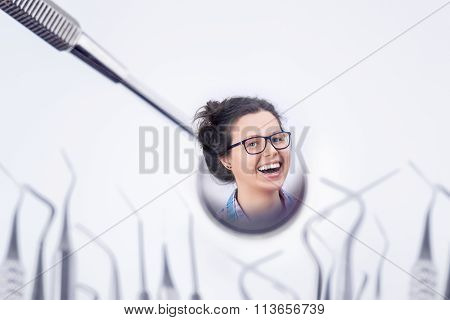 Cheerful Young Female Laughing In A Dentist's Mirror