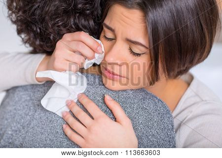 Crying woman is hugging her sister.