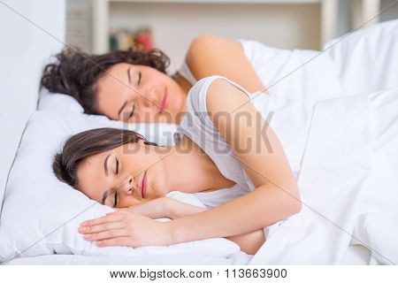 Two sisters are sleeping in the bed.