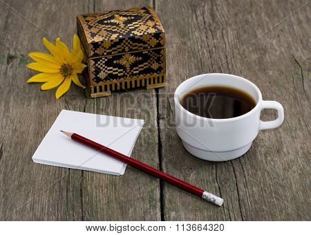 Casket, Coffee, Pencil With Paper And A Yellow Flower