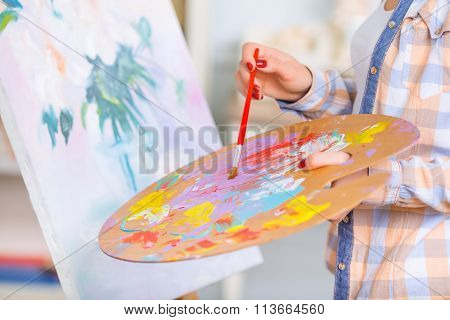 Young girl is busy oil-painting.