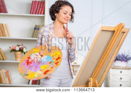 Young woman is checking her piece of art.