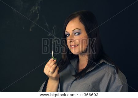Beautiful Brunette Holds A Smoldering Match