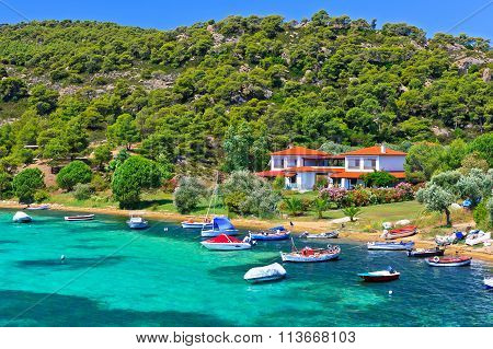 Boats And Yachts Moored Near The Villa In A Secluded Location On The Aegean Sea