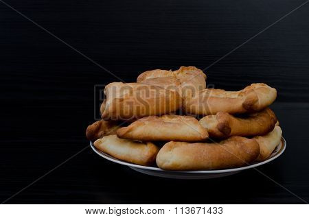 Plate with fresh fragrant pies on a black wooden table lunch echpochmak. Copy space