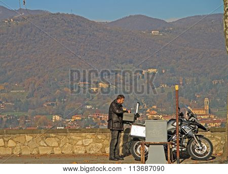 man is eating against the background of hills in Bergamo, Italy