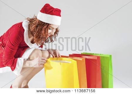 Happy Smiling Caucasian Ginger Santa Helper Girl With Colorful Shopping Bags. Posing Against White B