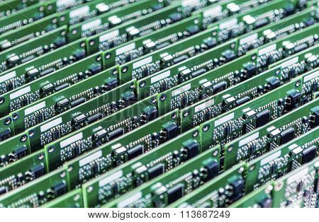 Lots Of Printed Circuit Boards With Mounted And Soldered Componentry Arranged In Rows Together.