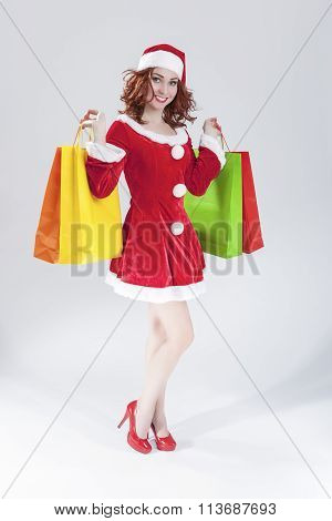Full Length Portrait Of Smiling Sexy Caucasian Ginger Santa Helper Girl With Plenty Of Colorful Shop