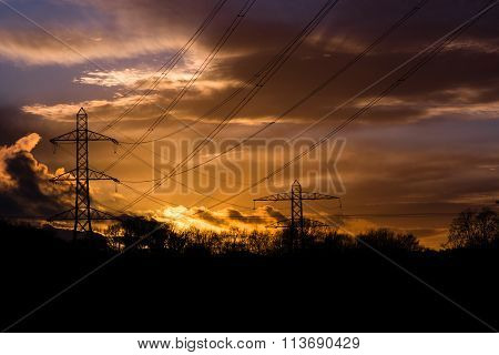 Industrial landscape with cables in front of sunset