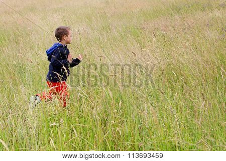 Child Running On Meadow