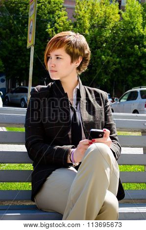 Young Business Woman With A Phone Working Outdoor Sitting On The Bench
