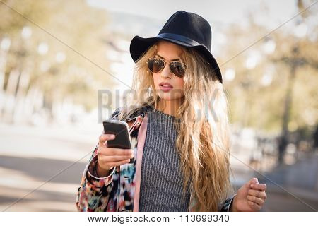 Young Woman Looking At Her Smartphone In Urban Background