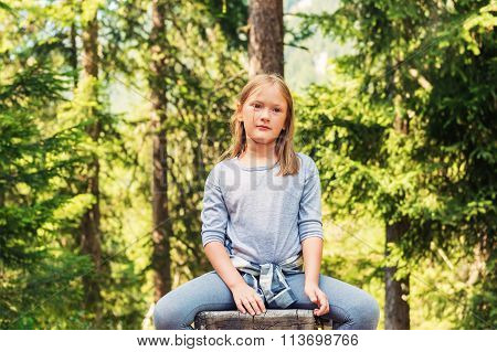Close up portrait of a cute little girl hiking in a forest