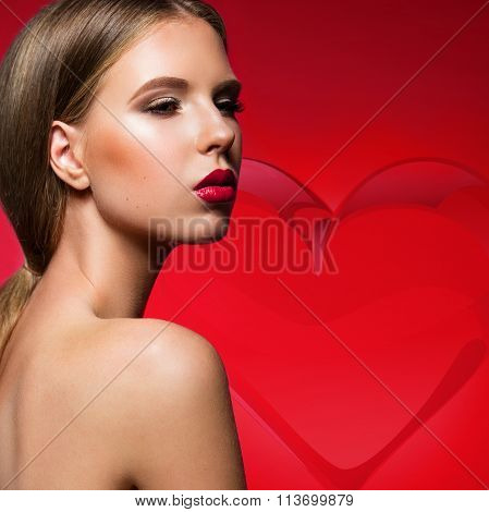 Beautiful woman with evening make-up, red lips and heart on background. Smoky eyes. Fashion photo.