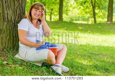 Portrait Laughing 50 Year Old Woman In The Park Dedicated To Knitting