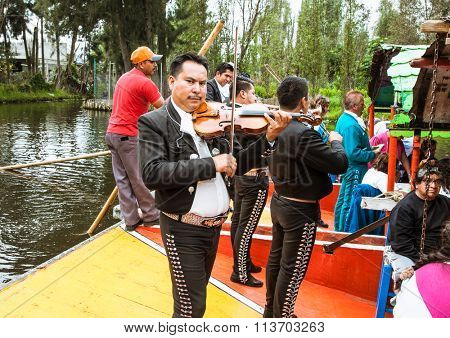 XOCHIMILCO,MEXICO- DEC 3. 2015: Mariachi guitar players and dancers performs on drifting barges on  Dec 3. 2015  in Mexico city. System of canals in Mexico City measures about 170 km.