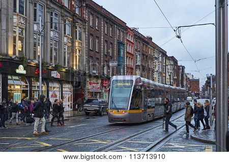 DUBLIN, IRELAND - JANUARY 05: The Luas, Dublin's tram system train, crossing pedestrian area in rainy day. January 05, 2016 in Dublin