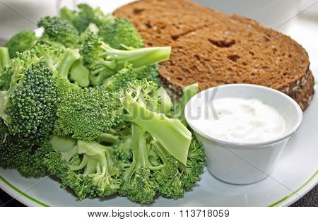 Nutritious Rye bread sandwich with a side of fresh Broccoli and a dipping sauce