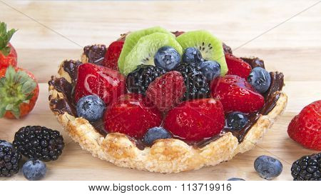 Fresh fruit in a tart on wood table