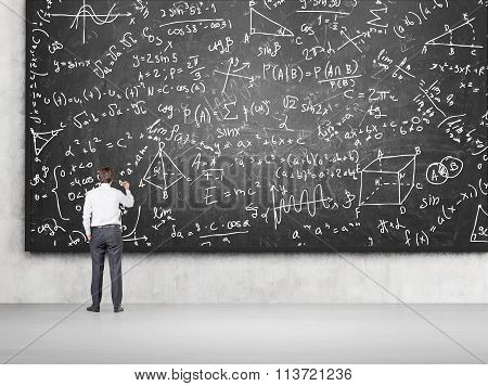 Man Solving Problems On Blackboard