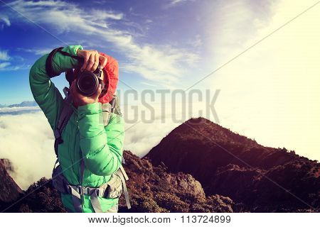 young woman hiker taking photo on  on mountain peak