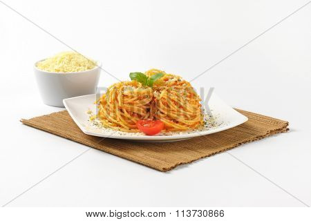 plate of cooked spaghetti with red pesto and grated parmesan cheese on brown place mat