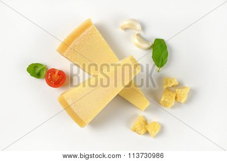 wedges and pieces of fresh parmesan cheese on white background