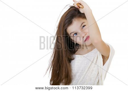 Hair care concept with portrait of little brunette girl brushing her unruly, tangled long hair isolated on white