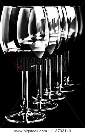 Row of red wine glasses  on a black background in vertical format