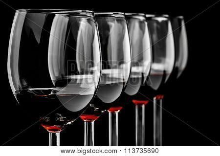 Row of red wine glasses  on black background in horizontal format