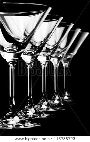Row of empty martini glasses on black background in vertical format