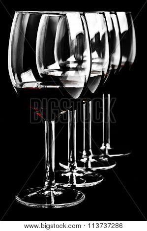 Row of red wine glasses  on black background in vertical format