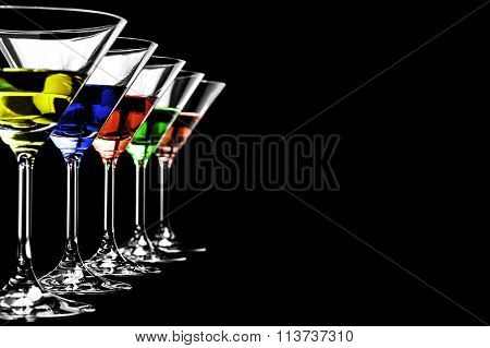 Row of martini glasses on black background in horizontal format
