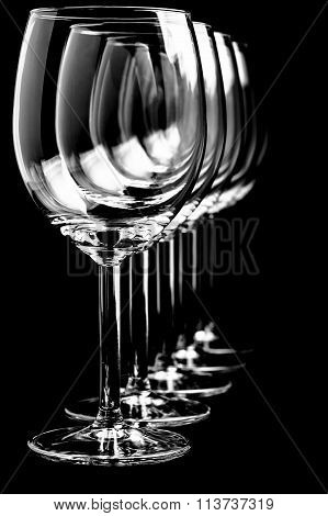 Row of empty wine glasses  on black background in vertical format