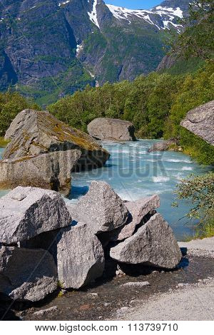 Norway. Water Flow From The Thawing Glacier Briksdayl In Mountains In The Summer Afternoon