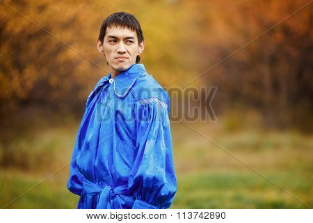 Confident, handsome man dressed  traditional national costume blue, standing still. Blurred backgrou
