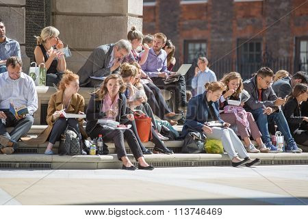 LONDON UK - SEPTEMBER 10, 2015: Office workers, business People having a lunch in the park next to s